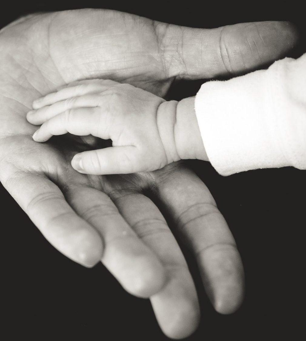 Babyhand auf der Hand des Vaters